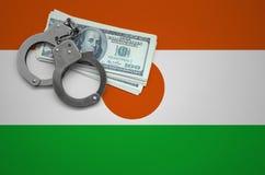 Drapeau du Niger avec des menottes et un paquet de dollars Le concept de casser la loi et les crimes de voleurs photo libre de droits