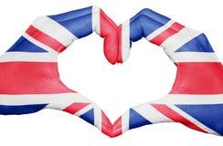 Drapeau du Royaume-Uni peint sur des mains formant un coeur d'isolement sur le fond blanc, le ressortissant BRITANNIQUE et le con Image libre de droits
