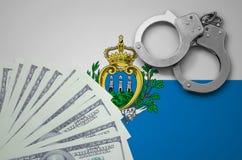 Drapeau du Saint-Marin avec des menottes et un paquet de dollars Le concept des opérations bancaires illégales dans la devise des images libres de droits