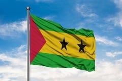 Drapeau du Sao-Tomé-et-Principe ondulant dans le vent contre le ciel bleu nuageux blanc images stock