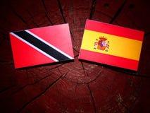 Drapeau du Trinidad-et-Tobago avec le drapeau espagnol sur un isola de tronçon d'arbre Photo stock