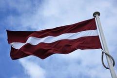 Drapeau du vol de la Lettonie en brise Image stock