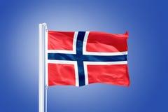 Drapeau du vol de la Norvège contre un ciel bleu Images stock