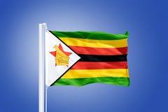 Drapeau du vol du Zimbabwe contre un ciel bleu Image stock