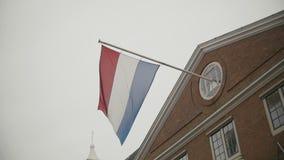 Drapeau du vol néerlandais sur le bâtiment à Amsterdam, Hollande, au ralenti banque de vidéos