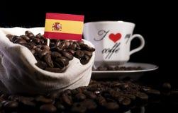 Drapeau espagnol dans un sac avec des grains de café sur le noir Photos stock