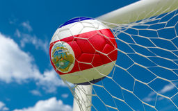 Drapeau et ballon de football de Costa Rica dans le filet de but Image stock