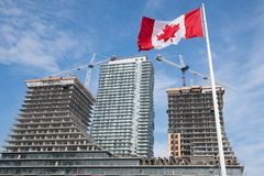 Drapeau et grues canadiens sur le chantier de construction à Toronto, Canada images libres de droits