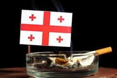 Drapeau géorgien avec la cigarette brûlante dans le cendrier d'isolement sur le noir Photos stock
