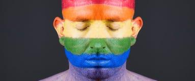 Drapeau gai peint sur le visage d'un homme. Photographie stock libre de droits