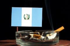 Drapeau guatémaltèque avec la cigarette brûlante dans le cendrier sur le noir Photos stock