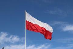 drapeau horizontal Blanc-rouge sur un mât de drapeau se développant dans le vent contre un ciel bleu avec les nuages légers Symbo image libre de droits