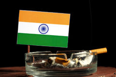 Drapeau indien avec la cigarette brûlante dans le cendrier sur le noir Photo libre de droits