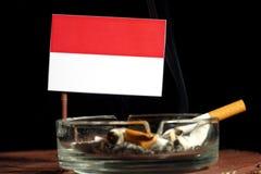 Drapeau indonésien avec la cigarette brûlante dans le cendrier sur le noir Photographie stock libre de droits