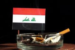 Drapeau irakien avec la cigarette brûlante dans le cendrier sur le noir Images libres de droits