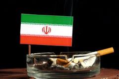 Drapeau iranien avec la cigarette brûlante dans le cendrier d'isolement sur le noir Images libres de droits