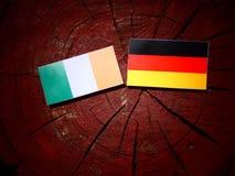Drapeau irlandais avec le drapeau allemand sur un tronçon d'arbre images stock