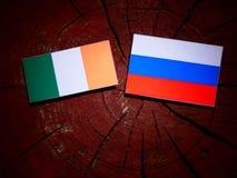 Drapeau irlandais avec le drapeau russe sur un tronçon d'arbre photos libres de droits
