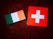Drapeau irlandais avec le drapeau suisse sur un tronçon d'arbre photo libre de droits