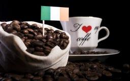 Drapeau irlandais dans un sac avec des grains de café d'isolement sur le noir Images stock