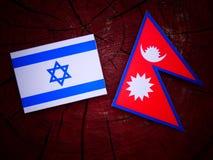Drapeau israélien avec le drapeau de Nepali sur un tronçon d'arbre d'isolement Photographie stock
