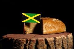 Drapeau jamaïcain sur un tronçon avec du pain photos stock