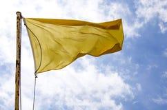 Drapeau jaune ondulant sur le ciel bleu Image libre de droits