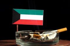 Drapeau koweitien avec la cigarette brûlante dans le cendrier sur le noir Image stock
