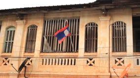 Drapeau laotien pendant d'une maison communiste détériorante de style dans Suvannakhet banque de vidéos