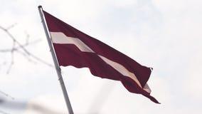 Drapeau letton flottant dans la haute de vent dans le ciel pendant un coucher du soleil d'or d'heure - capital de Riga, Lettonie  banque de vidéos