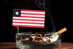 Drapeau libérien avec la cigarette brûlante dans le cendrier sur le noir Photos libres de droits