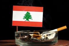 Drapeau libanais avec la cigarette brûlante dans le cendrier sur le noir Photos libres de droits