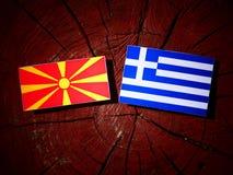 Drapeau macédonien avec le drapeau grec sur un tronçon d'arbre d'isolement Photos stock