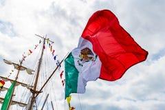 Drapeau mexicain énorme tissant sur le fond de ciel Images stock