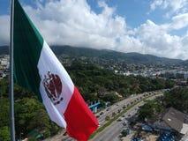 Drapeau mexicain ondulant sur la baie d'Acapulco, Mexique, vue aérienne Photo stock