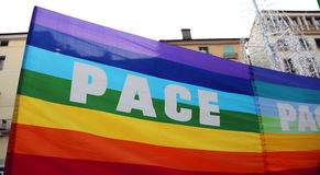 Drapeau multicolore de paix pendant une démonstration des activis de paix Images stock