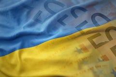 drapeau national de ondulation coloré de l'Ukraine sur un fond de billets de banque d'argent d'euro photos libres de droits