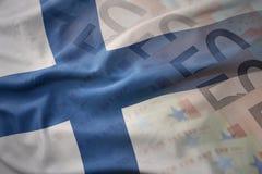 Drapeau national de ondulation coloré de la Finlande sur un fond de billets de banque d'argent d'euro image stock