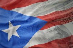 Drapeau national de ondulation coloré du Porto Rico sur un fond américain d'argent du dollar photographie stock