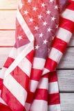 Drapeau plissé des Etats-Unis sous la lumière du soleil Photographie stock libre de droits