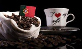 Drapeau portugais dans un sac avec des grains de café sur le noir Photo libre de droits