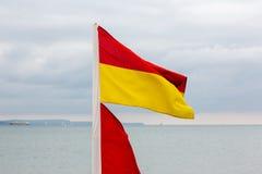 Drapeau rouge et jaune de maître nageurs sur la plage Photos libres de droits