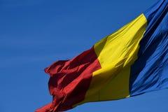 Drapeau roumain dans le vent un jour ensoleillé avec le ciel bleu clair image stock