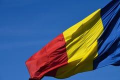 Drapeau roumain dans le vent un jour ensoleillé avec le ciel bleu clair photo libre de droits
