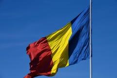 Drapeau roumain dans le vent un jour ensoleillé avec le ciel bleu clair images libres de droits