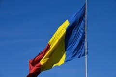Drapeau roumain dans le vent un jour ensoleillé avec le ciel bleu clair photo stock
