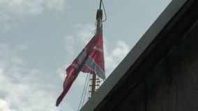 Drapeau russe flottant dans le vent sur un mât de drapeau contre le ciel bleu et les nuages clips vidéos