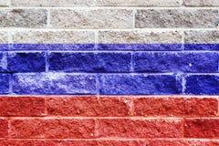 Drapeau russe peint sur un mur de briques de pierre de gris Photographie stock