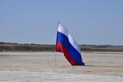 Drapeau russe sur le fond d'un lac salé Images libres de droits