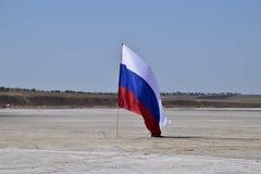 Drapeau russe sur le fond d'un lac salé Photographie stock